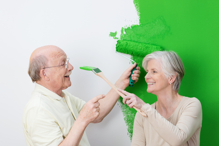Playful senior couple painting their house green with the man laughingly pointing a finger at his wife a she tries to dab paint on his nose with her brush photo