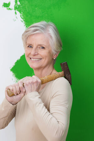 competent: Attractive competent elderly woman with a friendly smile standing holding hammer in front of a half painted wall while doing home renovations Stock Photo
