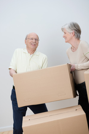 Senior couple moving house stacking brown cardboard cartons filled with their personal belongings as they pack everything up