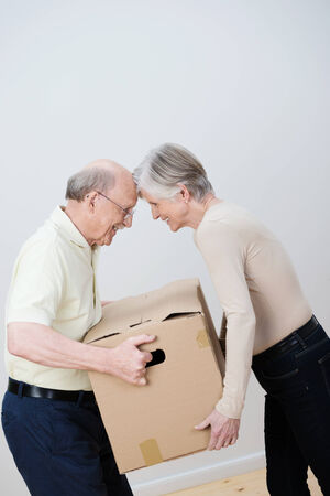 Playful elderly couple moving house bumping foreheads as they both try to carry the same cardboard carton photo