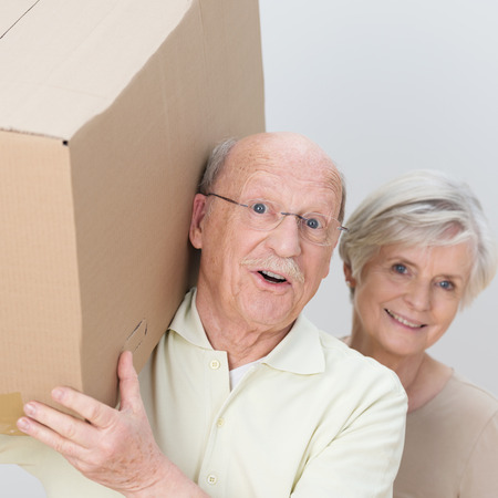 Energetic attractive senior couple moving home carrying out a cardboard box together and laughing at the camera, closeup of their faces