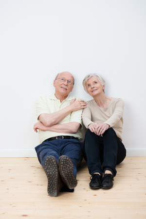 Elderly couple sitting daydreaming on the bare wooden floor in their living room in their new home as they imagine the placement of their personal belongings photo