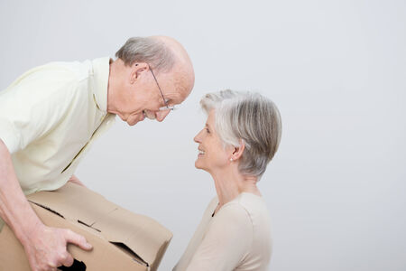 removals: Senior couple moving to a new home sharing a moment of tenderness as they smile at each other over a brown cardboard carton