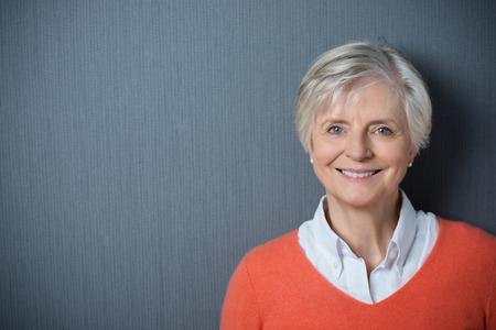 Aantrekkelijke grijsharige senior vrouw met een stralende glimlach poseren tegen een donkergrijze achtergrond met copyspace en vignettering