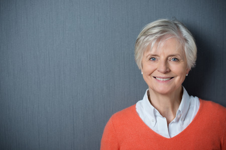 mature old generation: Attractive grey-haired senior woman with a beaming smile posing against a dark grey background with copyspace and vignetting Stock Photo