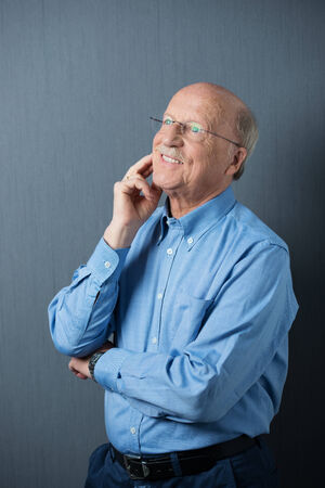 Elderly man in glasses standing thinking with his hand to his chin and a happy smile as he recalls fond memories photo