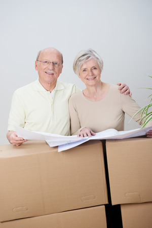 move in: Senior couple moving home planning their future as they stand with an open set of blueprints of the new property on a stack of cartons deciding where to place their belongings