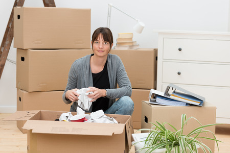 removals: Woman moving house packing her belongings kneeling on the floor next to a cardboard box wrapping items in paper