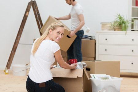 belongings: Beautiful woman moving house kneeling on the floor alongside a cardboard box and turning to smile at the camera as her husband uses a stepladder in the background