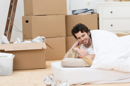 Loving couple sleeping on the floor on a mattress surrounded by cardboard boxes as they enjoy their first night together in their new home photo