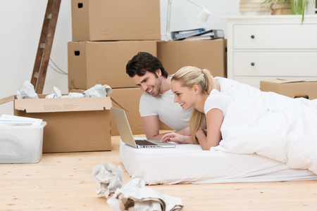 removals: Happy couple taking a break from moving lying on a mattress on the wooden floor in their new house checking their email on a laptop surrounded by cardboard boxes