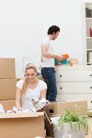 removals: Attractive young blond woman kneeling on the floor unwrapping items from a packing carton in their new home as her husband puts everything away in a teamwork concept Stock Photo