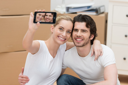 Smiling couple photographing themselves on a mobile phone as the pose surrounded by brown cardboard cartons in their new home photo