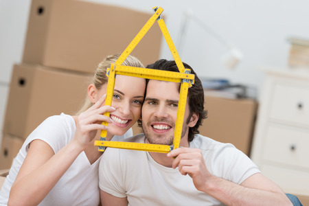 removals: Young couple dreaming of their new home grinning as they hold up a builders ruler shaped as the frame of a house as they pose in front of stacked brown cartons in anticipation of a move