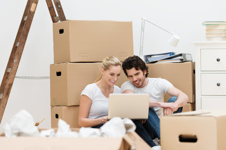 removals: Young couple surrounded by packing boxes smiling as they use their laptop to make contact with friends while moving house Stock Photo