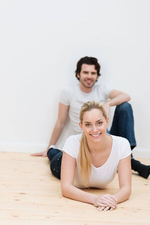 Young couple relaxing on the bare wooden floor of their new home as they wait for their furniture to arrive with the woman lying facing the camera smiling photo