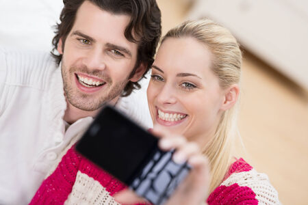 photographing: Smiling couple pose withb their heads close together for a self portrait on their smartphone Stock Photo