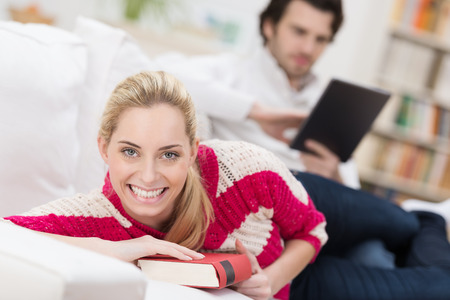 Beautiful smiling woman relaxing at home with a book on a sofa looking into the camera while her husband reads in the background Stock Photo - 26101629