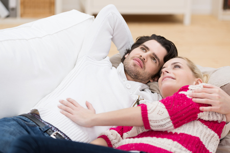 Young couple relax in each others arms on a sofa lying on their backs staring dreamily up into the air photo