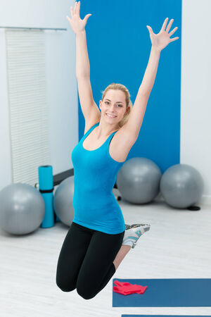 knees bent: Beautiful young blond woman jumping in a gym with her knees bent and arms extended as she works out doing her exercises Stock Photo