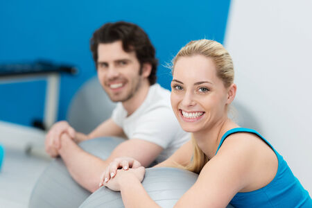 Smiling attractive couple doing pilates exercises in a gym together working out with large gym balls and pausing to smile at the camera with focus to the womans face photo
