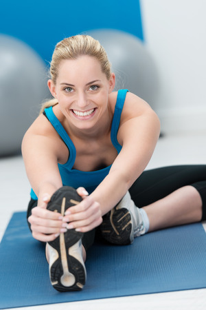 Beautiful young blond female athlete doing stretching exercises in a gym warming up on a mat before starting her workout and giving the camera a warm friendly smile photo