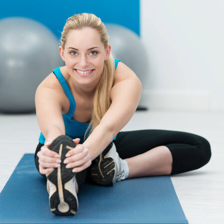 Beautiful woman doing stretching exercises to warm and tone her muscles before she begins her workout in the gym sitting on a mat holding her feet Stock Photo - 26101641