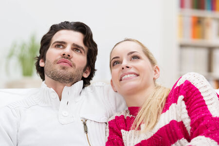 affective: Low angle view of a smiling attractive couple sitting close together on a sofa watching something above the viewers head and smiling with appreciation