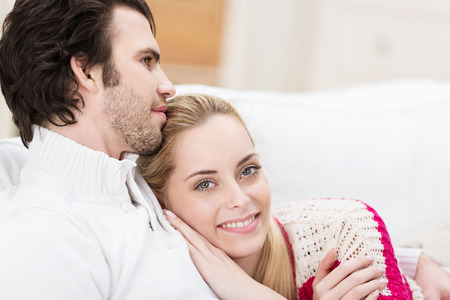 Smiling affectionate woman cuddling her husband lying on his chest with a beautiful contented smile , closeup and focus to her face Stock Photo - 26101642