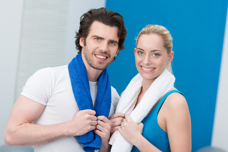 Happy athletic young couple at the gym standing smiling at the camera with their towels draped around their necks photo