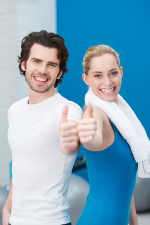 Enthusiastic young couple at the gym giving a thumbs up of approval with big beaming smiles full of vitality