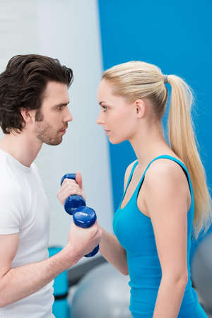 Intense young couple working out with dumbbells standing face to face exercising together and egging each other on to greater achievements photo