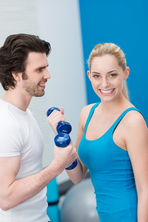 Beautiful young woman working out in a gym with dumbbells together with a handsome young male friend as they tone and strengthen their arm muscles photo