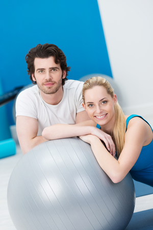 Young couple posing together in a gym with a Pilates ball with the beautiful blond woman giving the camera a warm friendly smile in a health and fitness concept photo