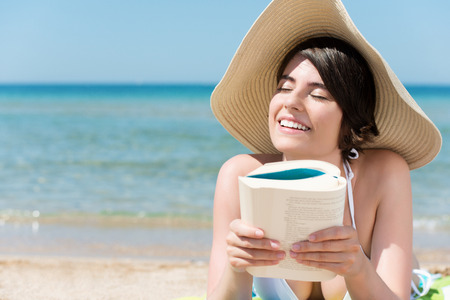 Relaxing woman in hat reading book in the beach photo