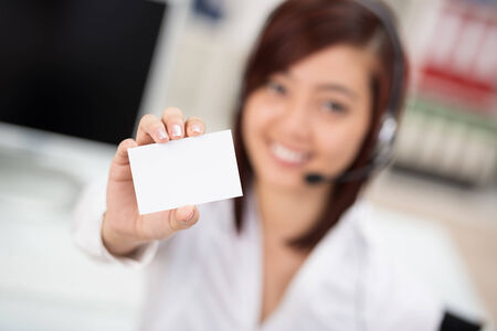 out of focus: Young businesswoman wearing a headset holding out a blank white business card fro your attention with focus to the card