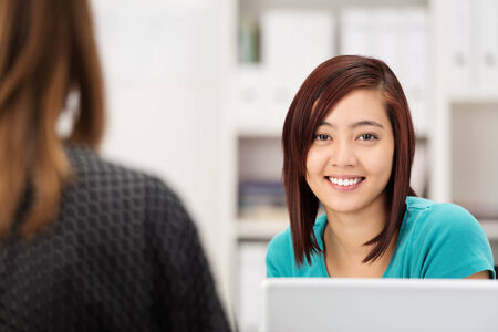 Attractive young Asian office worker sitting at her desk in the office chatting to a female co-worker and smiling at the camera photo