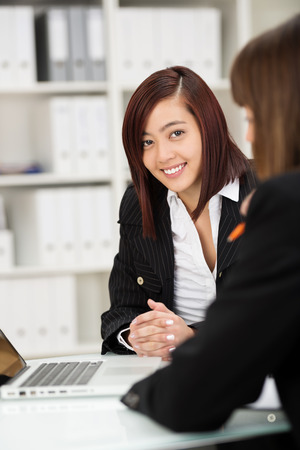 Two businesswomen working together as a team in the office sitting at a desk sharing a laptop with focus to a friendly Asian woman facing the camera with a smile