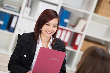 Lachende jonge Aziatische vrouw in een sollicitatiegesprek zitten praten met de arbeidsbemiddelaar met haar curriculum vitae in haar handen