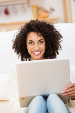Beautiful young African American student sitting on the floor in her living room with her laptop on her knees looking at the camera with a lovely friendly smile photo
