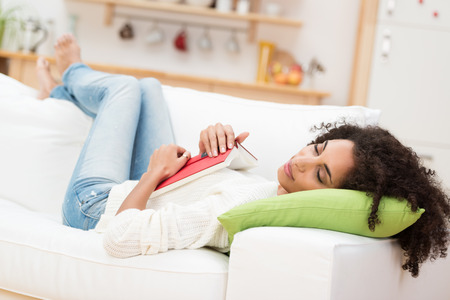relaxed: Tired attractive young African American woman fallen asleep with her book on her stomach as she relaxes on her back on a sofa in the living room