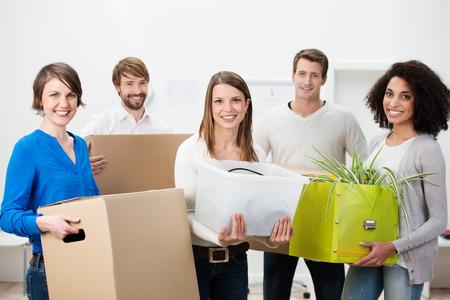 karton: Csoport különböző többnemzetiségű fiatal barátai segítenek költözés dolgozik a csapat hordozó karton dobozok tele személyes tárgyait, álló, mosolygós, fényképezőgép