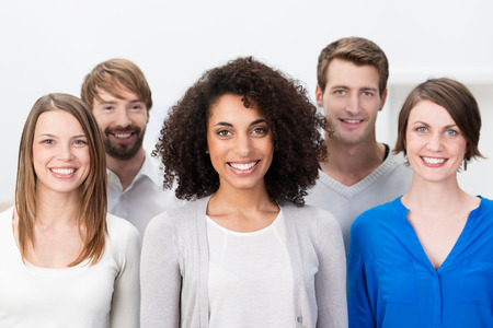 warmly: Multiethnic group of happy young friends posing grouped around an attractive African American woman in the centre as they smile warmly at the camera