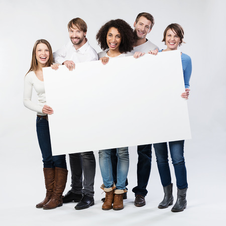 banner ad: Group of diverse multiethnic happy young people posing with a blank white rectabgular sign with copyspace for your advertisement or text on a grey background
