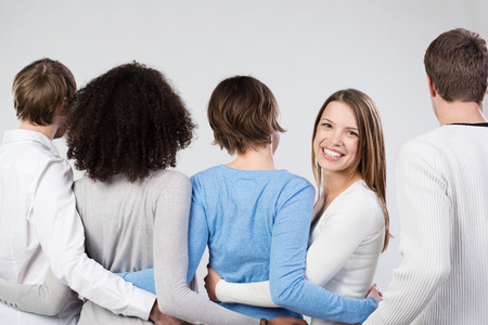 facing away: Group of friends linking arms facing away from the camera with an attractive young woman turning to look back with a beautiful friendly smile Stock Photo