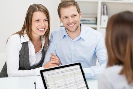 Aantrekkelijke jonge paar in een vergadering met hun bedrijf en beleggingsadviseur of verzekeringsagent zit aan een bureau in haar kantoor met een tevreden glimlach
