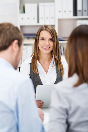 financial advisor: Smiling investment broker talking to clients as they sit together at a desk in her office, view between the young couples shoulders from behind
