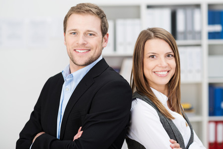 businessteam: Attractive successful business partners with a young man and woman posing back to back with folded arms smiling confidently at the camera