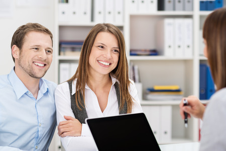 Smiling attractive young couple sitting in an office chatting to a business broker, insurance agent or adviser Stock Photo