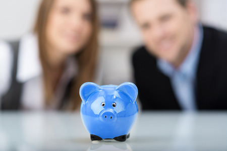 Conceptual financial image with a cute blue ceramic piggy bank sitting centered on a desk with a smiling successful professional couple in the background, focus to the piggy photo